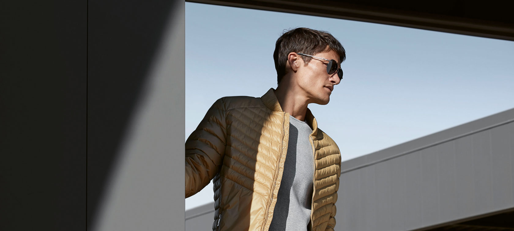 The picture shows a young model wearing the BMW Soft Down Jacket for men.